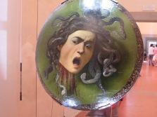"""Florence: Galleria degli Uffizi. Carravaggio, """"Testa di Medusa."""" (Parade shield)"""